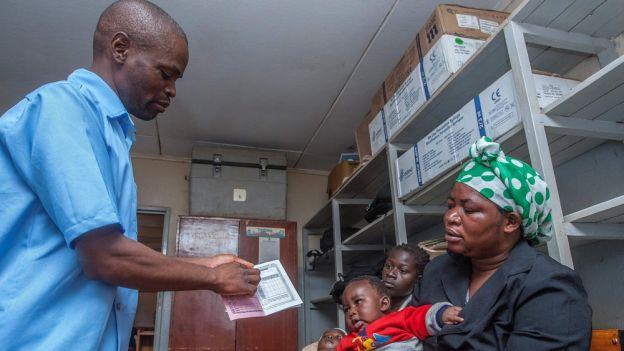 Sanitariusz wydaje kobiecie medyczny paszport do monitorowania programu szczepień