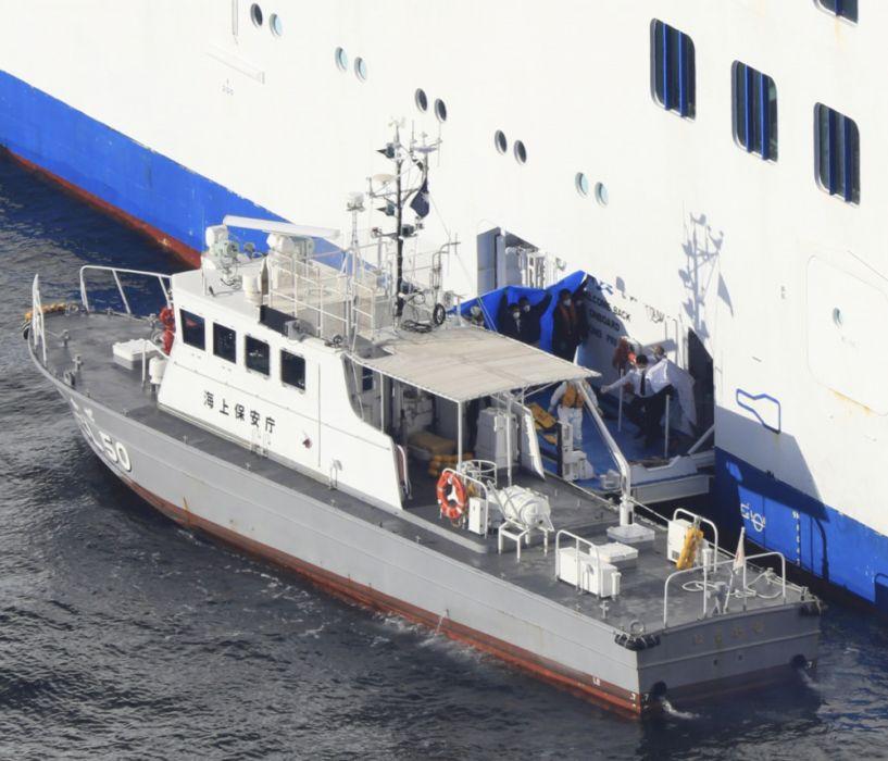 Strażacy prowadzą pasażerów, którzy mogli zostać zarażeni nowym koronawirusem w Jokohamie na statku wycieczkowym, 5 luty 2020 r. fot. Yomiuri Shimbun/Associated Press/East News