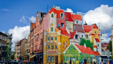 Przed sobą ma się mural z trębaczem i kotem, za sobą zabytkowy gotycki kościół św. Małgorzaty.