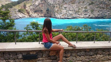 Dziewczyna siedząca na murku. Patrzy na zatoczkę Sa Calobra na Majorce